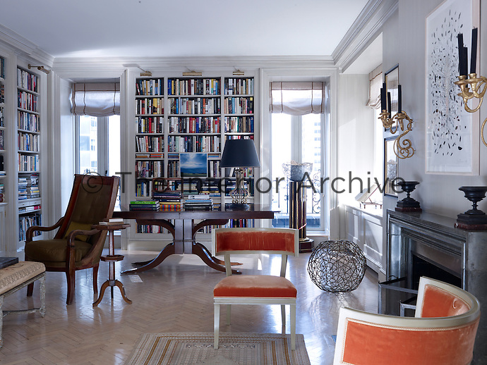 The living room is created as a library by day and a party space by night where a pair of library tables are designed with extra leaves to accommodate regular dinner parties