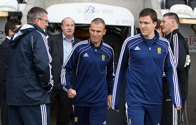 Gary Caldwell and Kenny Miller walk out past Craig Levein