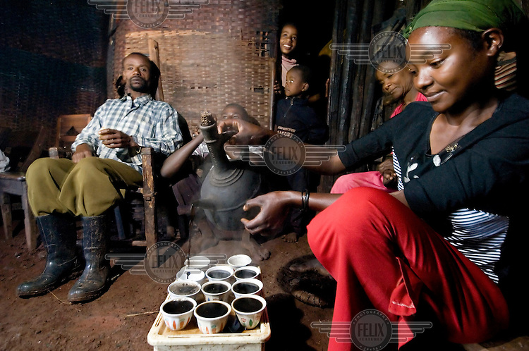 The wife of a local coffee farmer pours coffee for her family during a traditional coffee ceremony.