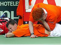 04-03-2006,Swiss,Freibourgh, Davis Cup , Swiss-Netherlands, Sjeng Schalken wordt aan zijn rug geholpen en kreunt het uit van pijn in zijn partij tegen  Marco Chiudinelli
