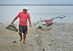 A fisher walks ashore on Jinamoc Island, part of the municipality of Basey in the Philippines province of Samar that was hit hard by Typhoon Haiyan in November 2013. The storm was known locally as Yolanda, and left most of the island's boats, nets, and houses destroyed. The ACT Alliance has been providing a variety of assistance to survivors here, and is planning a long-term rehabilitation program with residents.