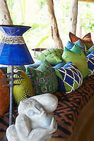 A metal lamp with a blue shade next to seating with brightly patterned cushions at the Singita Pamushana Lodge, Malilongwe Trust, Zimbabwe