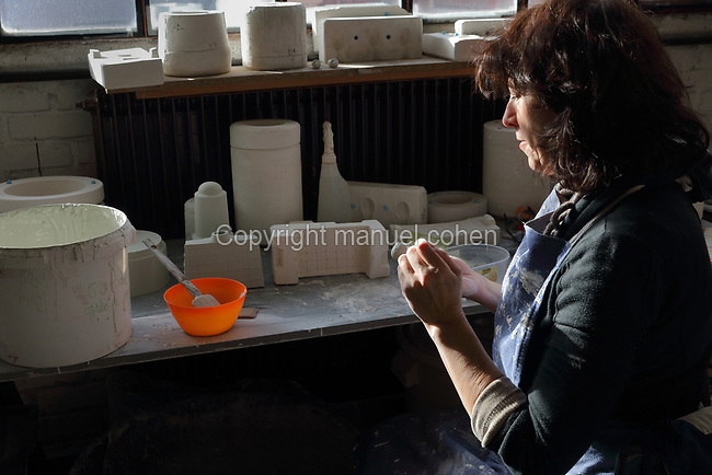 Ceramicist Valeria Polsinelli at work sculpting a female figurine from clay, photographed in 2017, in her studio in Montreuil, a suburb of Paris, France. Polsinelli creates everyday vessels, water jugs, jewellery and figurines and stoppers of female busts, with features and hairstyles from various world cultures. Picture by Manuel Cohen