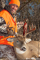 Hunter sitting beside a white-tailed deer he shot.