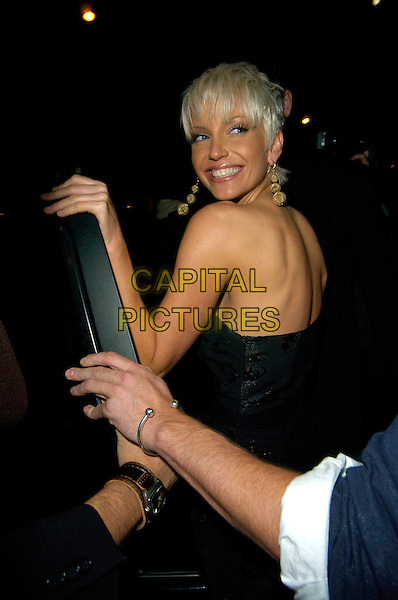 SARAH HARDING.Links of London - watch launch event, Il Bottaccio, Grosvenor Place, London, England..September 25th, 2007.half length black strapless earrings gold dress looking over shoulder .CAP/CAN.©Can Nguyen/Capital Pictures