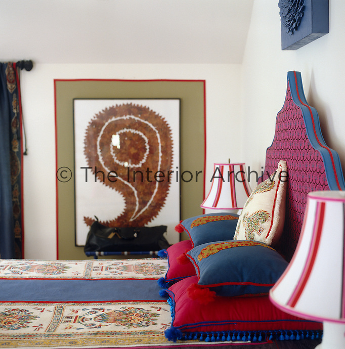 A leaf collage adorns the wall beside the bed which has a colourful headboard and cushions