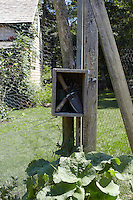 A small 'house' for a set of garden tools has been created on one of the uprights of the garden fence