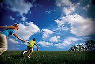 A young boy pulls his mother along as he runs towards a playground in a big green field