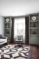Brown curtains and a brown pattern on the rug compliment the dark patina of the parquet floor in this living room, while the grey walls and pale soft furnishings keep the room light