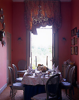 French windows open onto the garden from the salmon pink breakfast room