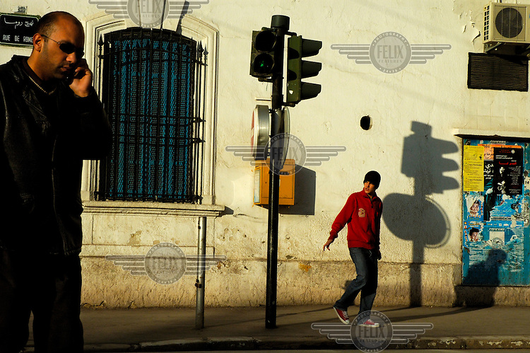 A morning commuter uses his mobile telephone on his way to work in the Ville Nouvelle (New Town) area in the city centre.