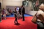 October 16, 2012. Raleigh, North Carolina.. Attendees return their stools at the end of the debate.. Locals gathered at the Contemporary Art Museum to see artist Jonathan Horowitz's simultaneous exhibitions about the presidential election titled ?Your Land/My Land?..  A room is divided in two, with blue carpet, democrats on one side, and red carpet, republicans, on the other. TV's on both sides are supposed to play either FOX news, red, or CNN, blue. Because of the audio delay between the 2 channels, both sides played CNN during the 2nd presidential debate..