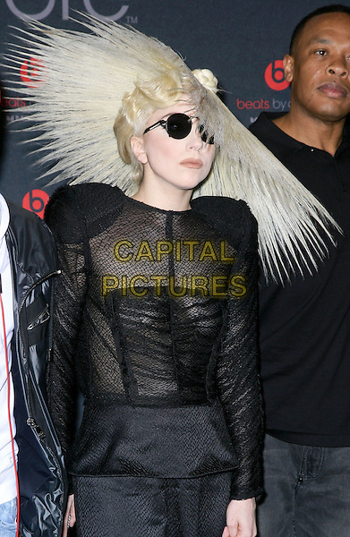 LADY GAGA (Stefani Joanne Angelina Germanotta) .attends the 2010 International Consumer Electronics Show (CES), the world's largest annual consumer technology trade show held at The Las Vegas Convention Center, Las Vegas, Nevada, USA, .7th January 2010..half length wig hair sunglasses round black sheer see through thru shoulder pads knitted knit ruched top dress hat hairspray.CAP/ADM/MJT.© MJT/AdMedia/Capital Pictures.