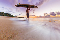 A surfer gets ready to paddle out at sunset, Sunset Beach, North Shore, O'ahu.