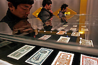 Visitors take a close look of some early Chinese currency during an exhibition about finance knowledge at the National Museum of China in Beijing, China. .