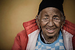 "An elderly woman at an ""Aged Shelter"" in Pokhara, Nepal. The ""Aged Shelter"" is a place for seniors to live, when they have no other family members to look after them. The shelter has no running water, cooking is done over a fire, and there are no nurses or doctors available."