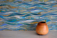 Oasis, a handmade mosaic shown in Peacock Topaz and Aquamarine jewel glass, is part of the Silk Road collection by Sara Baldwin for New Ravenna.<br />