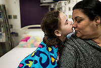 8-year old Beatrice Lipp kisses her mother Elaine in an hospital room at Boston Children's Hospital. Beatrice has been in and out of Hospitals for the last 5 years. Now at Boston Children's Hospital, she is part of a social robotic experiment between Boston's Children Hospital and the Massachusetts Institute of Technology (MIT). The goal of the experiment is to determine whether a so called 'Huggable' teddy bear, a social robotic stereotype, can have therapeutic value for children who have to endure long hospital stays. The bear's talking and movements are remotely controlled by Hospital Staff from outside of the room.