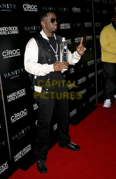 """SEAN """"DIDDY"""" COMBS.grand opening of Vanity Nightclub at Hard Rock Hotel and Casino, Las Vegas, Nevada, USA, .2nd January 2010..full length sunglasses holding bottle of vodka jacket cross necklace black  white hand finger gesture .CAP/ADM/MJT.©MJT/Admedia/Capital Pictures"""