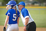 A first base coach gives instructions to a runner on first base.