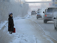 A woman on the side of a road in the city centre of Yakutsk.