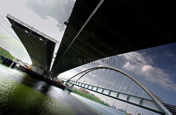 ROTTERDAM - In het Rotterdamse havengebied wordt gewerkt aan de langste, en laatste voorbouwbrug van Nederland, de Dintelhavenverkeersbrug, onderdeel van de snelweg A15. Eén spoorbrug en twee betonnen verkeersbruggen vervangen de oude stalen brug die vanwege de aanleg van de Betuwespoorlijn onvoldoende capaciteit had. Net als de Lekbrug in Vianen, zijn de bruggen vanuit de hamerstukken elke week met behulp van bekisting, een paar meter verlengd. De bruggen worden opgebouwd van hoge sterktebeton, rusten op twee oeverpijlers en krijgen een overspanning van 192 meter. COPYRIGHT TON BORSBOOM