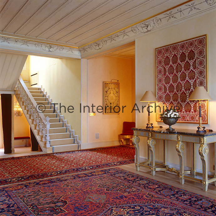 Classical and Arabic motifs are combined in the decoraton of this entrance hall, in the use of brightly coloured textiles and more delicate frieze painting on marbelised cream walls