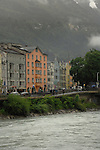 People walking past river Inn against the background buildings and forested mountain, Tyrol, Innsbruck, Austria.