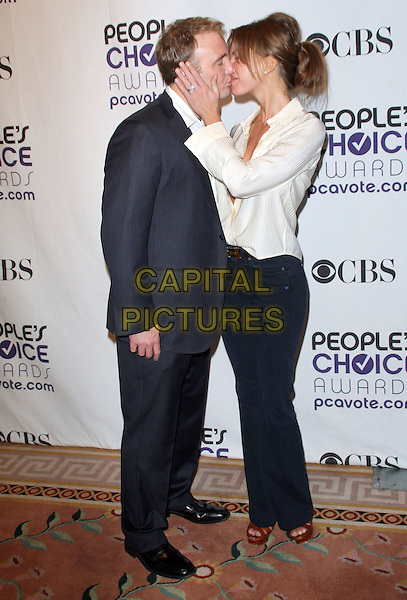 NIKKI COX & JAY MOHR .People's Choice Awards Nominees Announcement held at The Peninsula Hotel, Beverly Hills, California, USA, .10th November 2008..full length black grey gray suit white shirt blouse trousers cream low cut kissing kiss .CAP/ADM/KB.©Kevan Brooks/Admedia/Capital PIctures