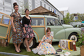London, UK, 18 May 2013. Three models in vintage dress pose with a Morris Minor 1000 for the centenary of the flower show. Press preview day at the RHS Chelsea Flower Show, London.