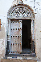 Zanzibar, Tanzania.  Door to House of Tippu Tip, Stone Town.  The door is carved in the South Asian style, with rounded top.  It shows the date 1309 in the Muslim calendar, equivalent to 1891 in the Gregorian.