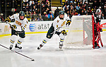 26 November 2010: University of Vermont Catamount forward Wahsontiio Stacey (9), a Senior from Kahnawake, Quebec, and forward Josh Burrows (22), a Senior from Prairie Grove, IL, skate behind the Huskies' net during play against Northeastern University at Gutterson Fieldhouse in Burlington, Vermont. The Huskies came back from a 2-0 deficit to earn a 2-2 tie against the Catamounts. Mandatory Credit: Ed Wolfstein Photo