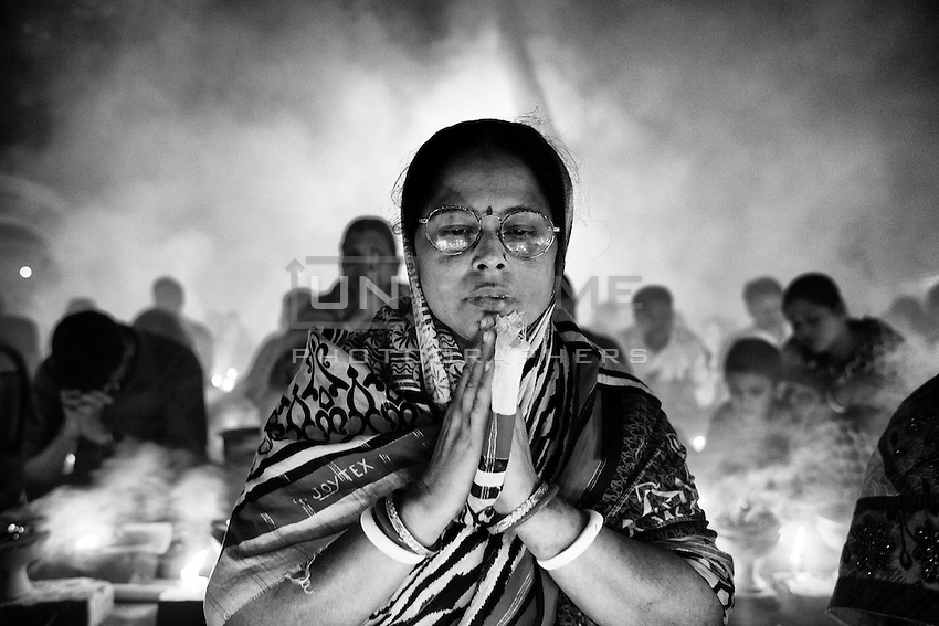 A Hindu woman prays during the Kartik Brati or Rakher Upobash religious festival in Barodi,  Near Dhaka, Bangladesh