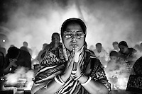 A Hindu woman prays during the Kartik Brati or Rakher Upobash religious festival in Barodi,  Near Dhaka, Bangladesh