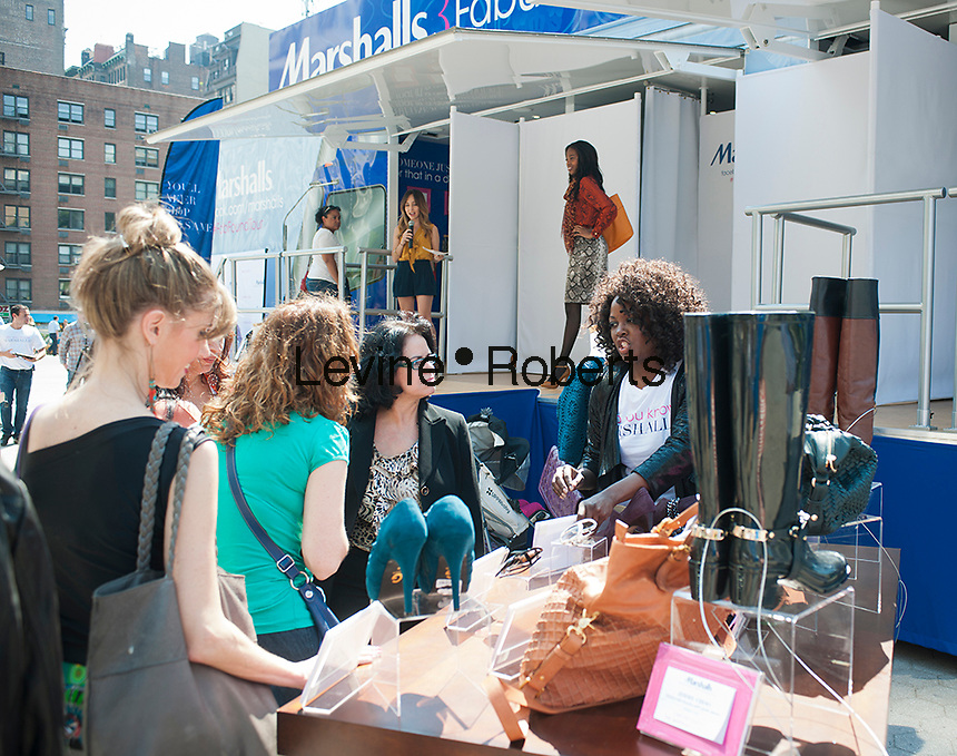"An employee promotes products during Marshalls Fabulous Found Fashion Tour promotional event by Marshalls Department Store in Union Square in New York on Thursday, September 13, 2012. The tour featuring a fashion show and a ""guess the price game"" was to promote the stores fall designer apparel. (© Richard B. Levine)"