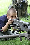 A child pretending to be shooting a machine gun at a reenactment