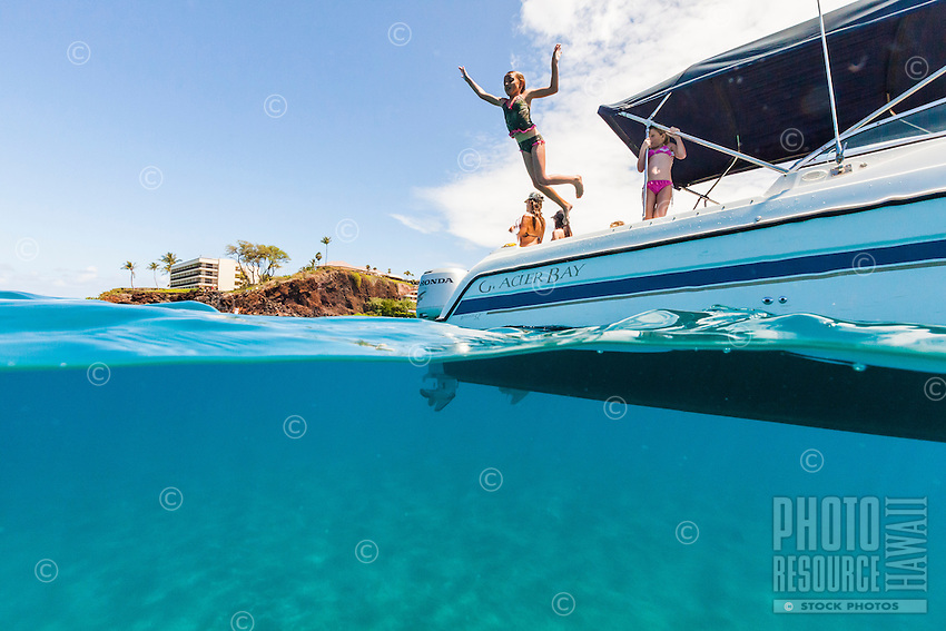 Split-level view of a girl jumping from a boat into the clear ocean water near Maui.