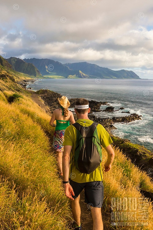 A couple hikes the Ka'ena Point Trail in the late afternoon, Mokule'ia, O'ahu.
