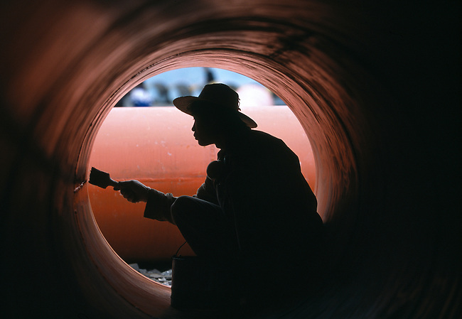 Man painting inside of huge orange drain or water pipe; laborer; industry; city of Fengjie, China, Asia; evening; 042203