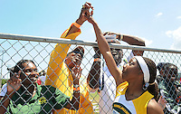 As her father Carl Cunningham, far right records the moment, Robin Reynolds of Jackson, high fives her coaches Teresa Smith, left and Donnell Jackson after she lands what would be a record setting 20 feet 6 1/4 inch long jump during the FHSAA Class 2A Track and Field Finals at the University of North Florida in Jacksonville, Florida Saturday April 28, 2012.(Kelly Jordan)