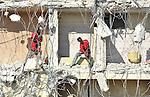 Men work scavenging recyclable material from a building in Port-au-Prince, Haiti, in the wake of a devastating earthquake that shook the Caribbean island nation on January 12.