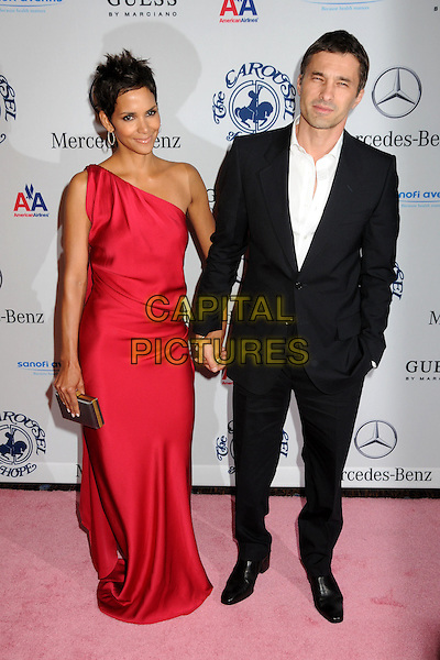 HALLE BERRY & OLIVIER MARTINEZ .32nd Anniversay Carousel of Hope Gala held at the Beverly Hilton Hotel, Beverly Hills, California, USA, .23rd October 2010..full length silk satin red one shoulder long maxi gold clutch bag holding hands couple white shirt black suit dress.CAP/ADM/BP.©Byron Purvis/AdMedia/Capital Pictures.
