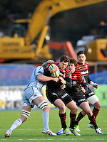 Hendon, England. Alex Goode of Saracens tackled during the LV= Cup match for the first professional rugby game on the artificial turf pitch made for rugby between Saracens and Cardiff Blues at Allianz Park Stadium on January 27, 2013 in Hendon, England.