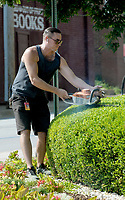 NWA Democrat-Gazette/DAVID GOTTSCHALK Bryan Wise, grounds keeper with the Walton Arts Center, trims Monday, July 2, 2018, the shrubs in a garden area near the intersection of Dickson Street and School Avenue at the center. Wise started early on the east side job in an effort to avoid the higher temperatures in the afternoon.