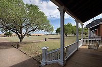 View across the parade ground to the Enlisted Men's barracks, from the Commanding Officer's quarters, on Officers' Row, at Fort Davis National Historic Site, a US army fort established 1854, in a canyon in the Davis Mountains in West Texas, USA. The house was begun in 1867 under Lieutenant Colonel Wesley Meritt, but has been refurbished to the time of Colonel Benjamin Grierson, commander of the black Tenth US Cavalry, and his family, who lived here 1882-85. The fort was built to protect emigrants, mail coaches, and freight wagons on the trails through the State from Comanche and Apache Indians. After the Civil War, several African-American regiments were stationed here. By the 1880s, the fort consisted of one 100 buildings, housing over 400 soldiers. It was abandoned in 1891, but many buildings have been restored and the compound now operates as a historical site and museum. Picture by Manuel Cohen