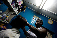 a woman cuts a customer's hair  while awaiting for the 50th anniversary of her countries' independence in the Jamestown neighborhood in Accra, Ghana on Sunday March 04 2007..