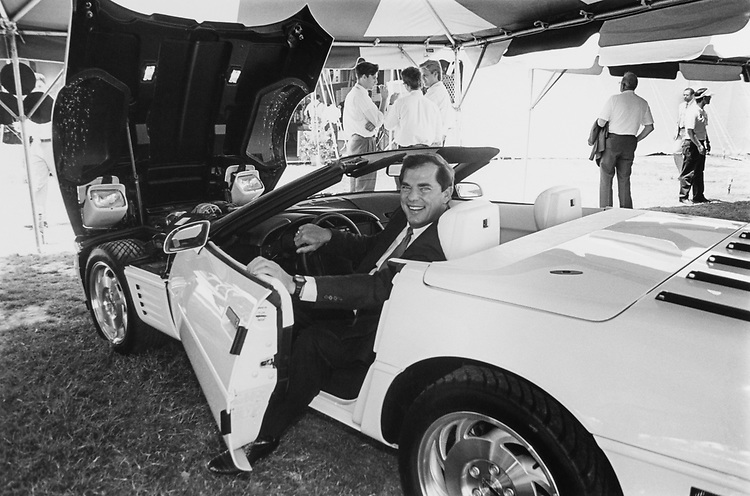 "Rep. Bill Sarpalius, D-Tex., poses in a white corvette (He has a red one just like it!) at the ""United Auto Workers"" exhibit on Mall, on May 27, 1993. (Photo by Laura Patterson/CQ Roll Call)"