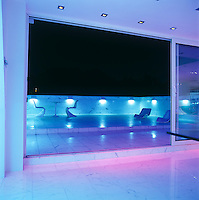 The glass doors of the living area open onto a vast terrace with a marble floor that shines at night