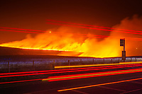 A long exposure frame of traffic passing a bus stop on the A62 road near Marsden as a moorland fire burns on Marsden Moor, near to Saddleworth, West Yorkshire, United Kingdom in the early hours of Wednesday 27th February 2019.