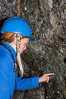 Kinder besichtigen ein Bergwerk unter Tage, entdecken Mineralien an den Wänden des Stollens